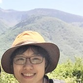 Image of a smiling Dasol Kim with a green, mountainous background